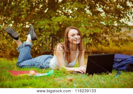 Student girl on grass with computer