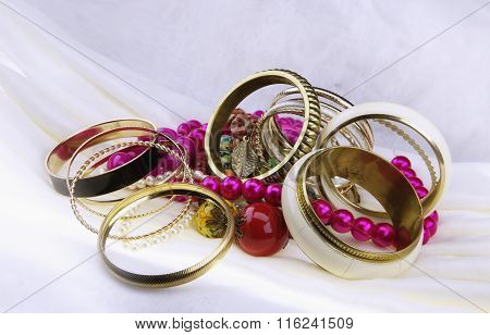 Golden bracelets and beads on a white cloth