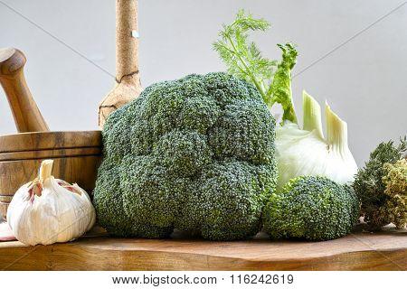 Fresh green broccoli, fennel, olive wood mortar and cutting board