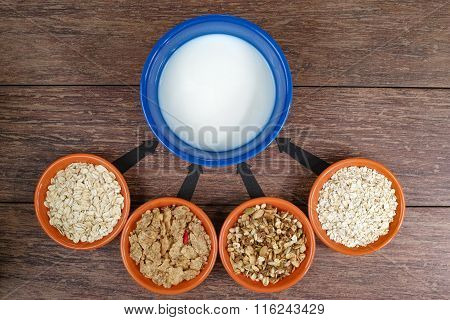 Four small bowls with different cereals and bowl with milk