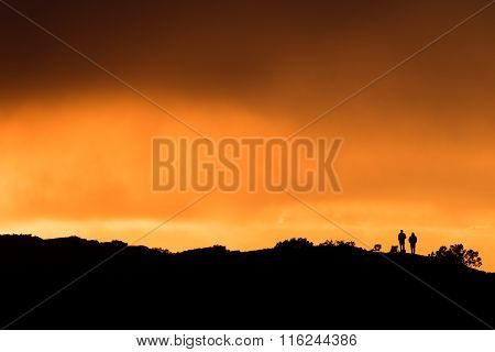 Two Spectators Standing On A Hilltop Watching Sunset