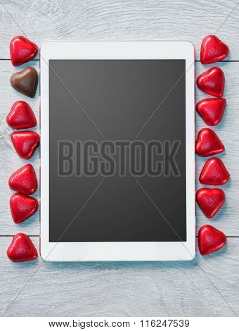 Digital Tablet and candy chocolates hearts.