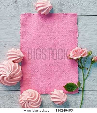 Pink paper and zephyrs for valentine's day on wooden background.