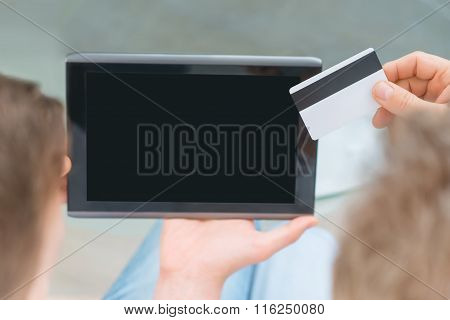 Father and adult son holding tablet