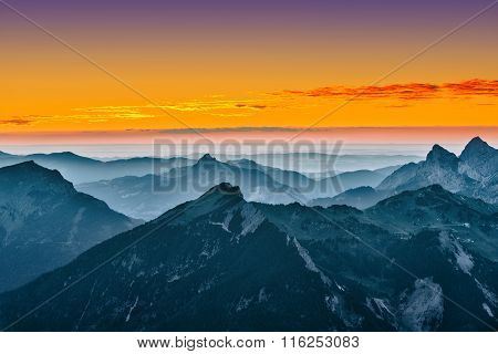 view over blue mountains with golden yellow sunset sky