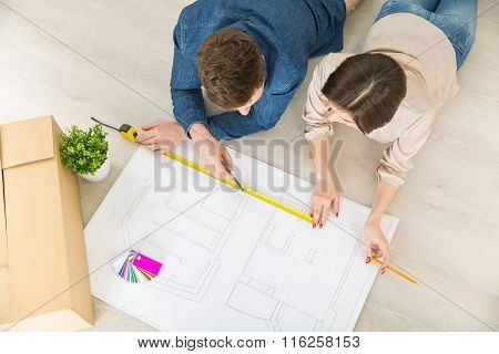 Happy couple drawing plan of their flat