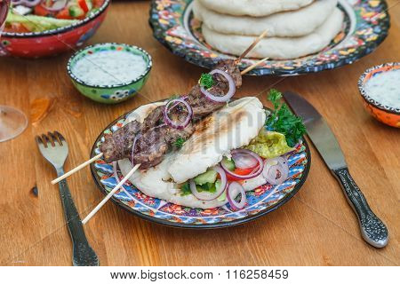 lamb kebab on a traditional greek plate
