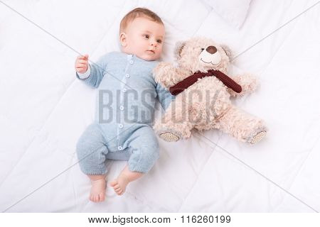 Infant boy lying in bed and grabbing teddy bear.