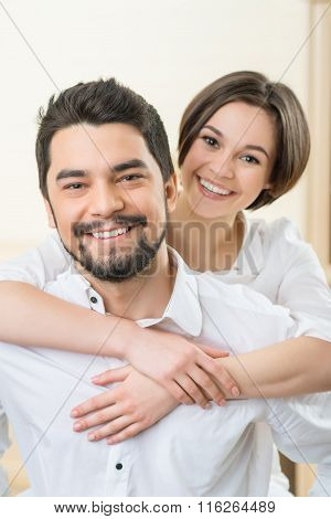Handsome man holding wife on the back