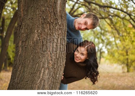 Couple Peeking Out From Behind A Tree