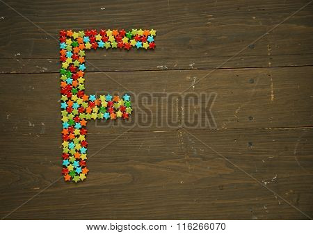 Letter F from alphabet made with star shape candy on a wooden background