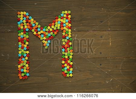 Letter M from alphabet made with star shape candy on a wooden background