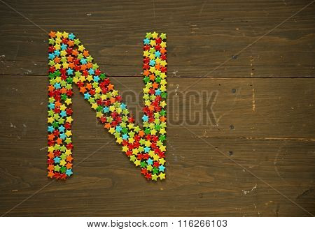 Letter N from alphabet made with star shape candy on a wooden background