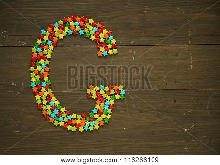 Letter G from alphabet made with star shape candy on a wooden background