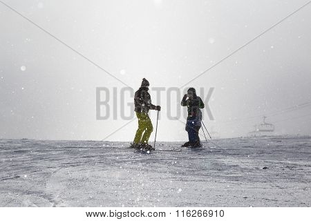 Two Skiers Take Photo On  Misty  Ski Slope .