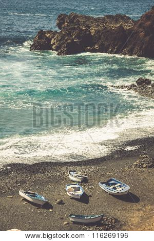 Atlantic Ocean On The Island Of Lanzarote. A Wonderful Rocky Beach With Fishing Boats Surrounded By