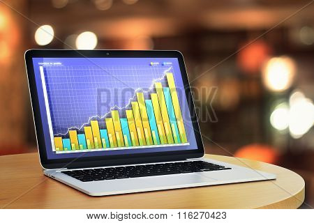 Business Chart On Lalptop Screen On Round Wooden Table