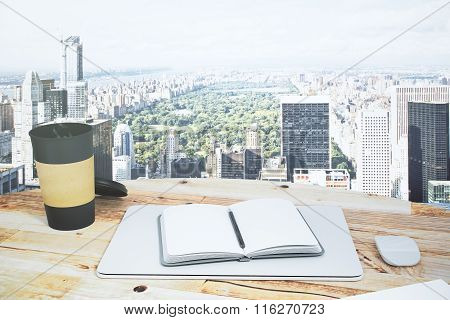 Open Notepad On A Wooden Table With A A Cup Of Coffee And A View To Central Park Of New York