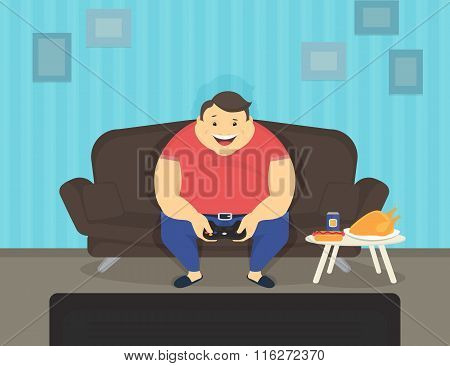 Fat man sitting at home on the sofa playing video games and eating