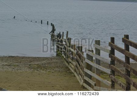 Fence by the beach caught in rising tide