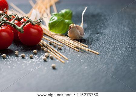 Pasta ingredients. Cherry-tomatoes spaghetti pasta fresh basil spices on a dark stone background