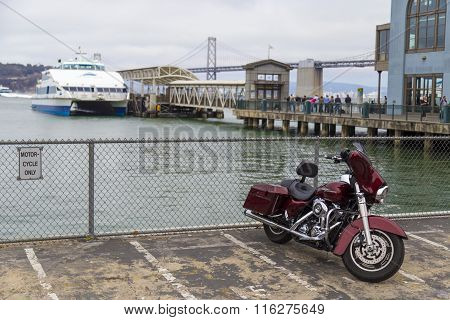 Harley Davidson Motorbike Parked On Embarcadero With Oakland Bay Bridge In Background, San Francisco