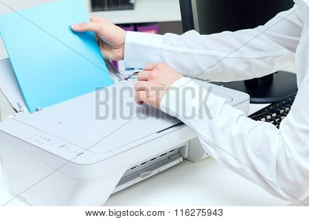 Man puts stack of paper to printer