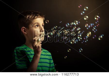Young Boy Blowing Soap Bubbles