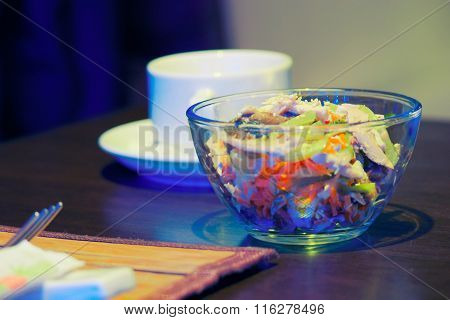 Glass bowl of salad and cup of tea on the table