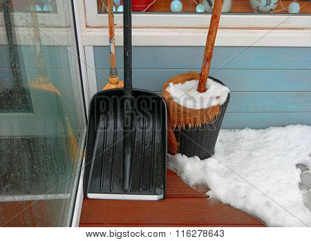 Black snow shovel standing in the snow leaning wall