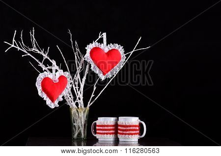 Pair of red hearts on a branch with two mugs
