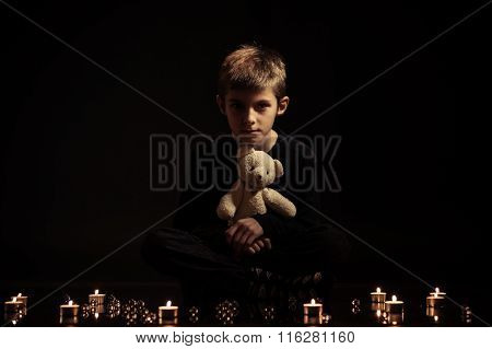 Boy With Teddy Bear Sits On The Floor With Candles