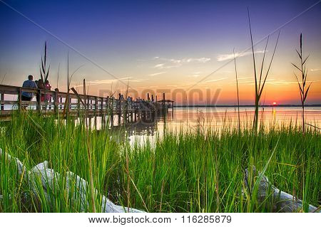 Fort Fisher, NC - August 14 2015 - Fort Fisher Air Force Recreation Center Kure Beach North Carolina USA: Tourists watch the sunset from the pier jutting out over the Cape Fear River.