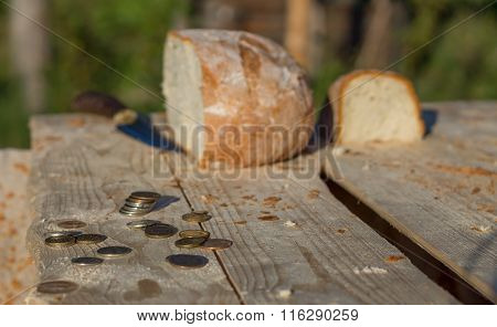 Bread On A Table With Coins And Knife. Defocused