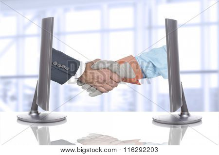 Handshake Over Desk in Business Office. Both hands are coming out of computer screens.