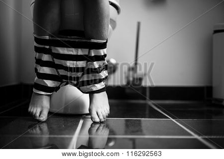 Underwear Around Legs Of A Young Boy On A Toilet