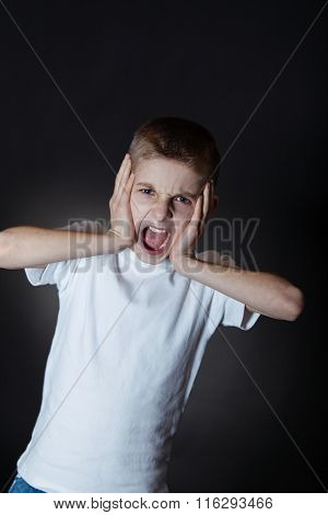 Irritated Boy Shouts At Camera With Hands On Face