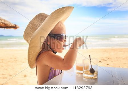Blond Girl In Large Hat Sunglasses Drinks Juice With Spoon