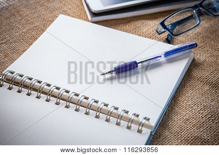 Still Life Of White Paper Note Book Page With Writing Pen Lying On Table Top And Eye Glasses Beside