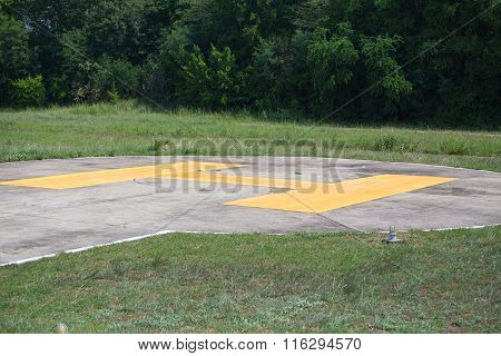 yellow H sign on helipad with forest background