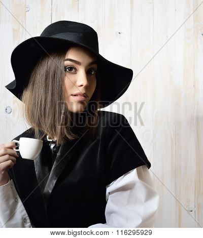 Young attractive woman in retro dress and hat drinking coffee over wooden background. Vintage stylization of lady with cup of coffee smelling delicate aroma of beverage. Image toned.