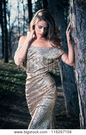 beautiful young woman in elegant glittering  dress  in wood lean on tree portrait