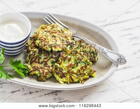 Zucchini Fritters With Herbs On A Ceramic Plate On A Light Wooden Background. Healthy, Vegetarian Fo
