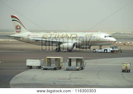 Towing aircraft Airbus A320-232 (A6-EIR) Etihad Airways in passenger terminal Abu Dhabi Airport