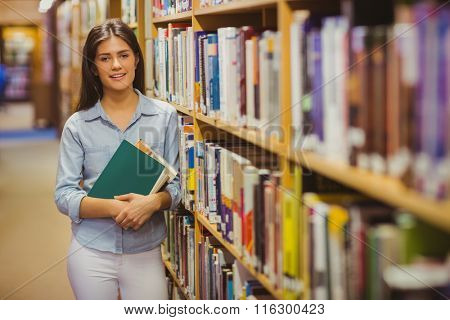 Smiling brunette student standing next to bookshelves while holding books in library