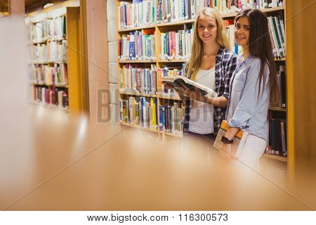 Pretty young students working together with book in library