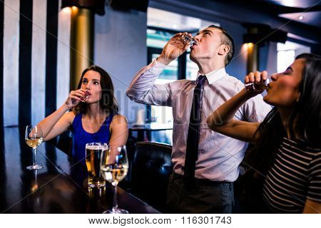 Friends drinking shots in a bar