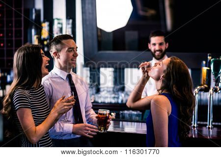 Woman having a shot with friends in a bar