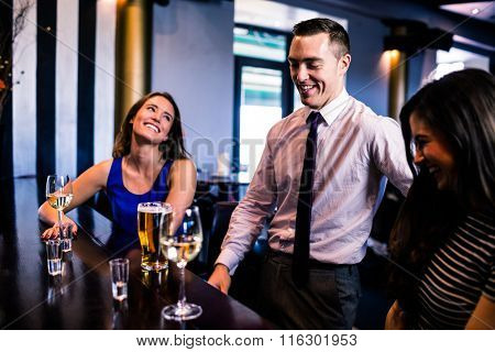 Friends talking and drinking in a bar