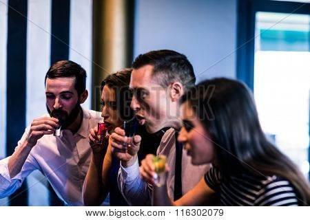 Friends drinking alcohol shots in a bar